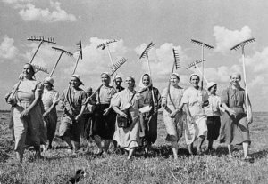 Female collective farmers holding rakes and walking through a field smiling.
